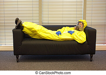 professional in protective clothing, mask and gloves, lying and relaxing on the couch in office