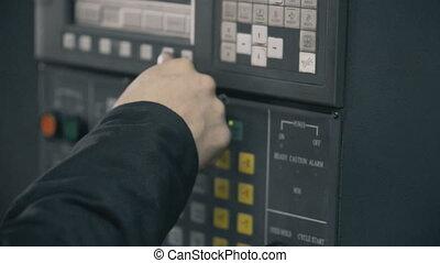 Professional industrial engineer adjusting modern machine settings CNC punching machine.
