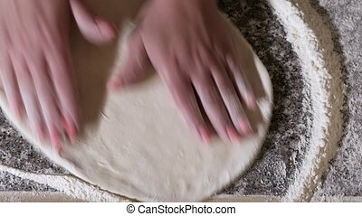 Professional italian baker kneading dough by hands on table. The process of cooking pizza by a cook in a restaurant.
