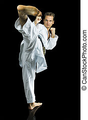 Professional karate fighter kicking. Isolated over black background.