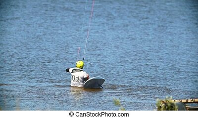 Professional kiteboarder in the water sets sail for...