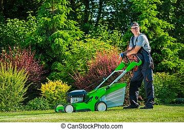Professional Lawn Mowing - Smiling Professional Gardener...
