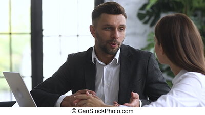 Head shot professional lawyer agent explaining insurance benefits to female client. Skilled businessman giving professional advice, negotiating new project details with partner employee at office.