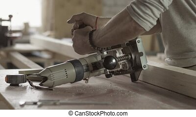 Professional locksmith adjusts plunge router by wrench....