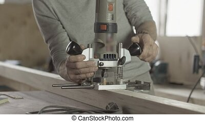 Professional locksmith fix plunge router on wooden board....