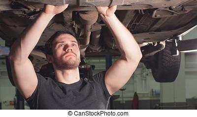 Professional Machine Repairman Checks the Bottom of the...