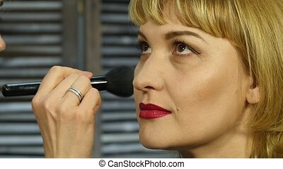 Professional make-up artist apply powder with brush on a client face. beauty fashion industry