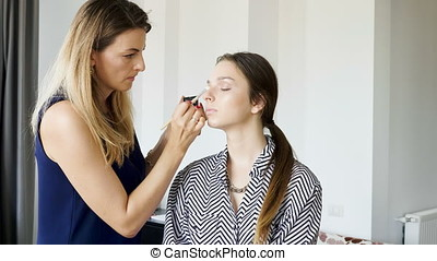 Professional make-up artist applying cosmetics on a client in the salon