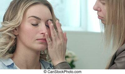 Professional make-up artist applying cream base eyeshadow ...
