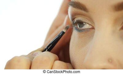 Professional make-up artist applying eyeliner on eye. makeup...