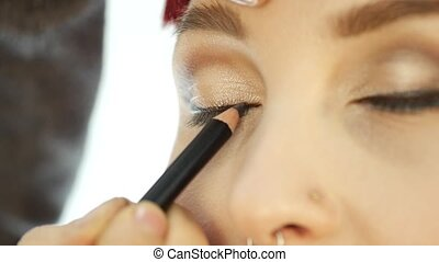 Professional make-up artist applying eyeliner on eye. makeup...