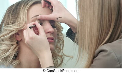 Professional make-up artist applying eyeliner on eyelid....
