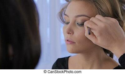 Professional make-up artist applying eyeshadow -...