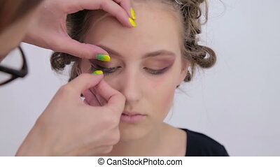 Professional make-up artist applying false eyelashes on...