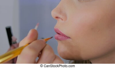 Professional make-up artist applying lip gloss on lips of...