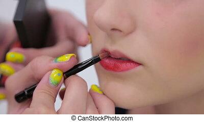 Professional make-up artist applying lipstick on lips of...