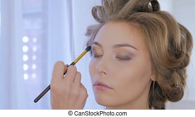 Professional make-up artist applying makeup on woman's face