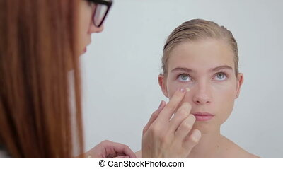 Professional make-up artist applying cream base eyeshadow...