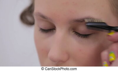 Professional make-up artist combing eyebrows of client