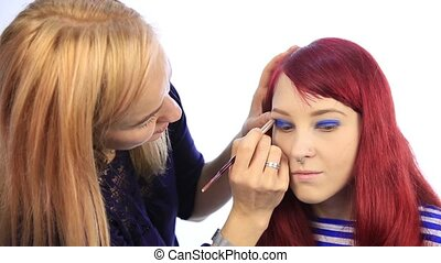 professional make-up artist dyes the eyes of the model....