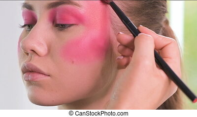 Professional make-up artist feathering creative matte...