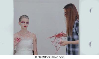 Professional make-up artist finishing halloween style for teen girl