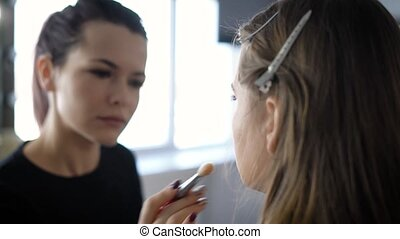 Professional make-up artist in the fashion industry is doing makeup young model who is sitting on a chair in her beauty studio. Girl with a brush in his hands blurred on the background.