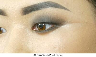 Professional make-up artist makes eye makeup of Korean girl...