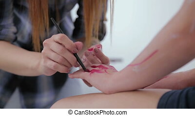 Professional make-up artist making body art in white room