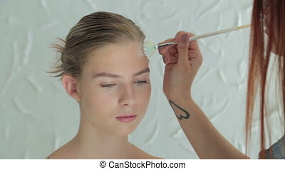 Professional make-up artist making face art in white room