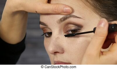 professional make-up artist paints eyelashes to beautiful client. fashion industry cosmetics