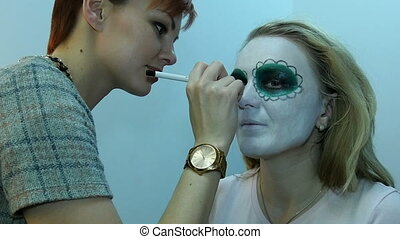 Professional make-up artist, using makeup to create a mask...