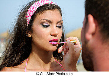 Professional make-up with a beautiful young woman by a beautician