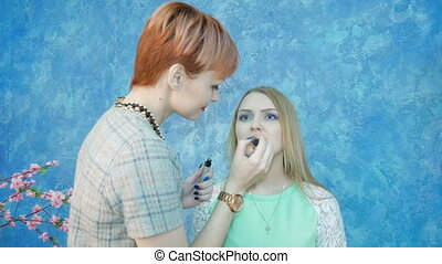 Professional makeup artist applies makeup to a beautiful...
