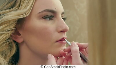 Professional makeup artist applying brown lipstick on lips of model