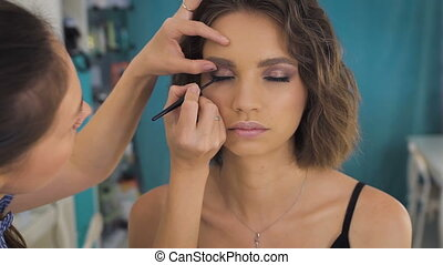Professional makeup artist applying make up on a beautiful...
