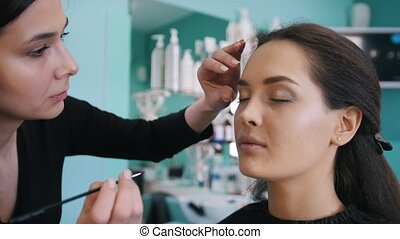 Professional makeup artist doing make-up with black...