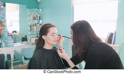 Professional makeup artist doing make-up with eye shadows,...