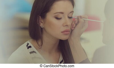 Professional makeup artist drawing arrow on the eyes of the model