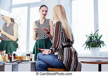 Nice young woman looking at her client