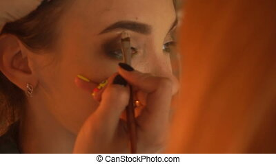 makeup artist paints eyes a young woman close-up