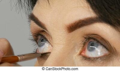 Professional makeup artist paints mascara on adult...