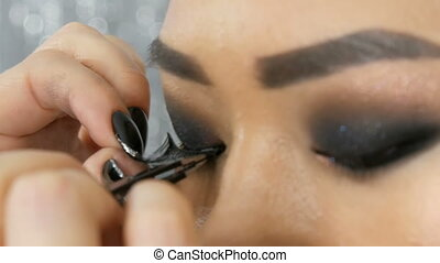 Professional makeup artist pastes false eyelashes on the...