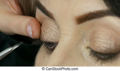 Professional makeup artist start to stick false eyelashes on...
