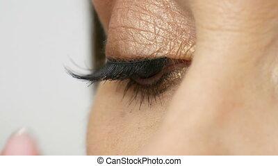 Professional makeup artist sticks false eyelashes on the...