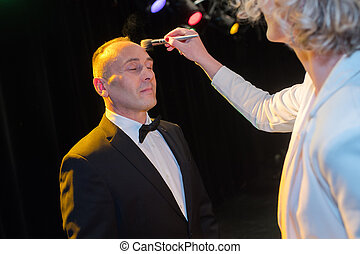 professional makeup artist working with man