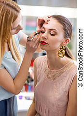 Attractive young woman having a professional makeup