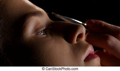 Professional makeup. Paint the eyebrows. Black. Closeup