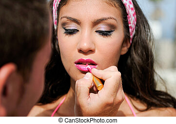 Professional makeup with a beautiful young woman having touches applied to her make up by a beautician