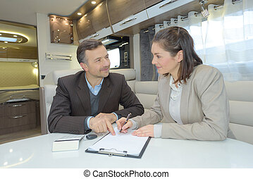 professional male and female business partners signing contract